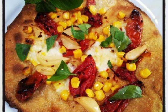fresh corn, roasted tomato & pickled garlic pizza with cornmeal crust